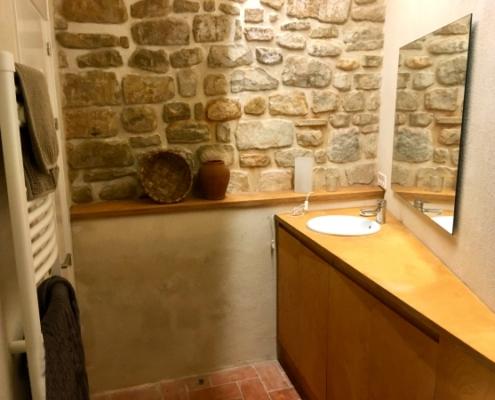 Baño con pared de piedra en casa rural
