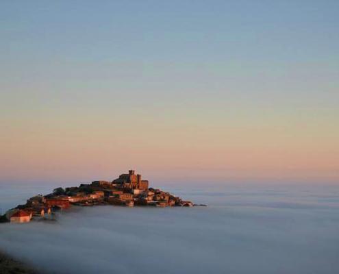 Vista de Ujué en la distancia, entre la niebla